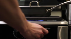 Stovetop burner turned on under pan Stock Footage