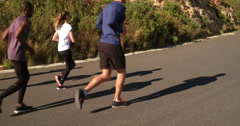 Athletic girl running outdoors with friends - stock footage