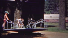 1954: Kids playground carosel spin hold tight fun playground party. Stock Footage