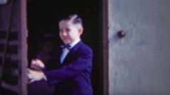 Stock Video Footage of 1954: Formal suit wearing boy leaves house cute face closeup.