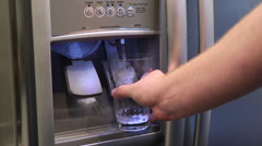 Water pouring into glass from fridge - stock footage
