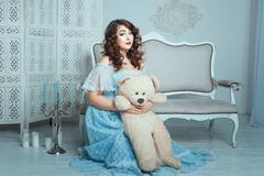 Plump woman with a toy bear. Stock Photos