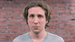 Adult man depict sincerely sympathy and sadness on camera. Brick wall. Audition Stock Footage