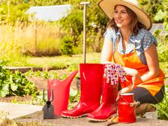 Female farmer and gardening tools in garden - stock photo