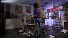 Creative chaos. In a cozy atmosphere. Artist painting picture in workshop Stock Footage