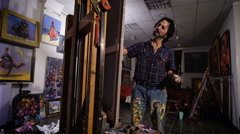 Stock Video Footage of perseverance. In a cozy atmosphere. Artist painting picture in workshop