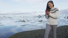 Phone app - woman using smartphone in Iceland by famous tourist destination - stock footage
