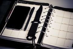 Plan for murderer - calendar, planner, cellphone, pen and knife as weapon Stock Photos