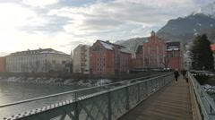 People walking and biking on Innsteg bridge, Innsbruck Stock Footage