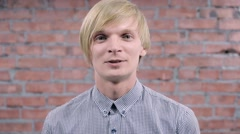 Young blonde man smiling and speak on camera. Rocking. Brick wall. Audition Stock Footage