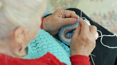 Closeup of a Grandmother Knitting Wool Socks on the Couch Stock Footage