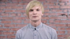 Adult blonde man try depict fright, fear, dread on camera. Brick wall. Audition Stock Footage