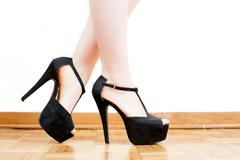 Young woman feet with black high heels and legs - stock photo