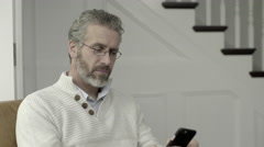 Senior Adult Male working from home on smart phone - stock footage