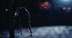Basketball Player Dribbling Ball on Court in Night Stock Footage