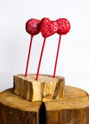 Stock Photo of Red cakepops  on the wooden old tree cut, white background