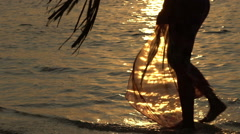 Woman walking along the surf line. Sunset on the ocean. Slow motion. - stock footage