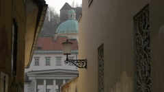 Narrow street between old walls with a vintage lamp post in Ljubljana Stock Footage
