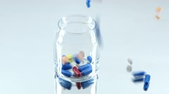 Colorful pills fall down into a bottle, on white, reflection Stock Footage