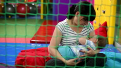 Mother is breastfeeding a baby in playground - stock footage