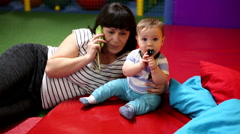 Mother talking on the cellphone and playing with baby in playground Stock Footage