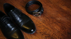 Close up of leather beltand  black stylish shoes isolated on a wooden Stock Footage