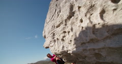 Rock climber holding to boulder and focused on route - stock footage