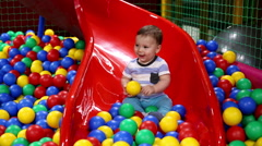 Baby on the chute with balls in playground - stock footage