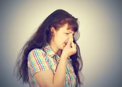 Young woman holding her nose because of bad smell Stock Photos