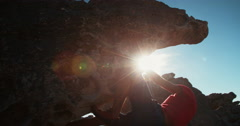Bouldering rock climber hanging beneath extreme overhang against blue sky - stock footage