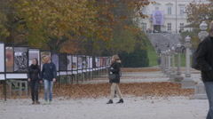 A couple and other people walking on Tivoli Park's main alley in Ljubljana Stock Footage