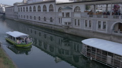 Boats floating up and down the Ljubljanica River in Ljubljana Stock Footage