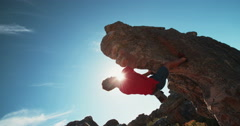 Low angle of extreme free climbing man hanging on rock Stock Footage