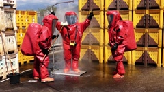 Firefighters dressing protective suit clean up after sealing a leaking container Stock Footage