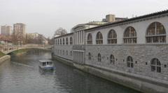 Boat floating on Ljubljanica River next to the Central Market in Ljubljana Stock Footage