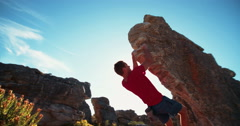 Bouldering rock climber hanging beneath extreme overhang against blue sky Stock Footage