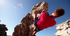 Low angle of extreme free climbing man hanging on rock - stock footage