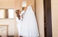 The bride in white bathrobe. Wedding preparations - stock photo