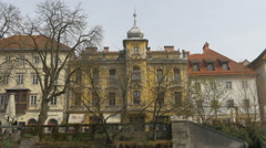 Yellow building with turret on the riverside in Ljubljana Stock Footage