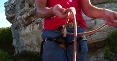 Closeup of rock climber hand's tying knot with belaying rope Stock Footage
