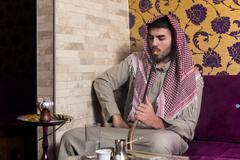 Islamic Man Smoking Shisha In The Arabic Cafe - stock photo