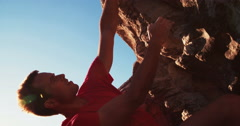 Rock climber hanging on boulder - stock footage