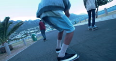 Multi-Ethnic Group of Skaters Skating Down Street at Beach Stock Footage