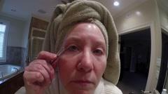 Mature Woman Tweezing Eyebrows Stock Footage