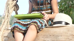 Girl using touch screen device on the sea - stock footage