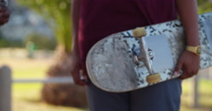 Back shot of two mixed race skaters holding their skateboards Stock Footage
