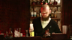 Handsome barman professional at posh bar making cocktail drinks - stock footage