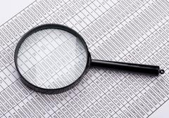 Magnifying glass lies on the statement printed paper - stock photo