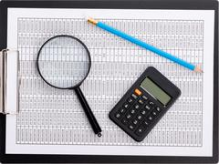 The report table under magnifying glass with calculator - stock photo
