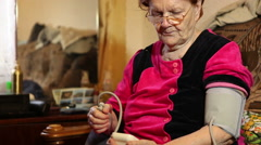 Elderly woman measuring blood pressure with an electronic tonometer Stock Footage